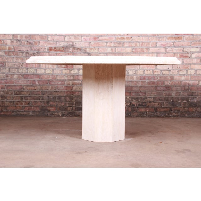 An exceptional modern Italian travertine octagonal pedestal dining, game, or center table Italy, Circa 1970s Measures:...