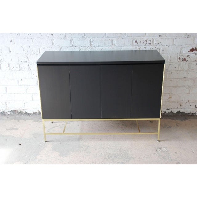 Offering a superb newly refinished ebonized Paul McCobb sideboard credenza for Calvin Furniture. This piece has a...
