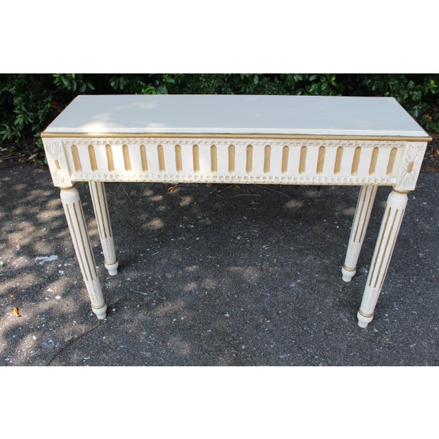 Solid oak Swedish console table with Gustavian hand carvings and fluted arrow legs. Refinished in a white patina with gold...