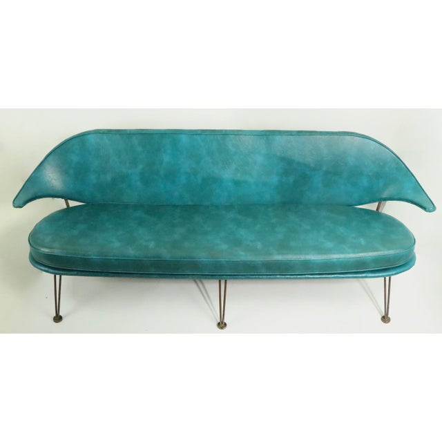 Unusual Mid Century sofa, loveseat, settee, having a wrought iron frame, and vinyl upholstered seat and back. The back is...
