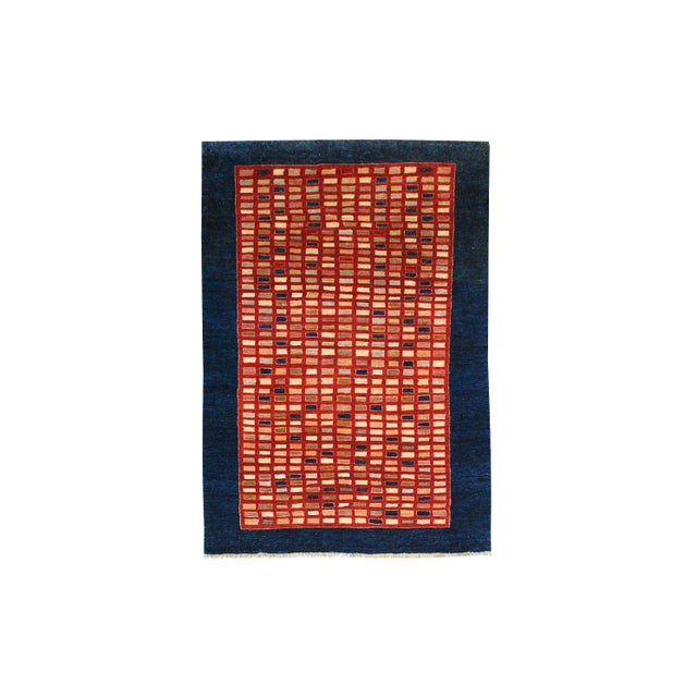 A hand-knotted Chobi wool rug in an all-over geometric design on a navy background. Overall pattern in red, yellow, green,...