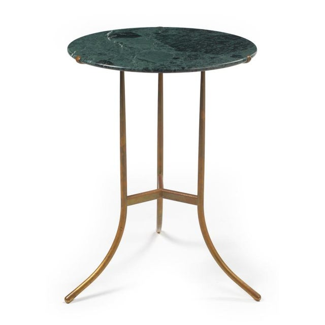 An exceptional occasional table comprising a circular polished Verde Issorie marble top supported on a tripod bronze base....