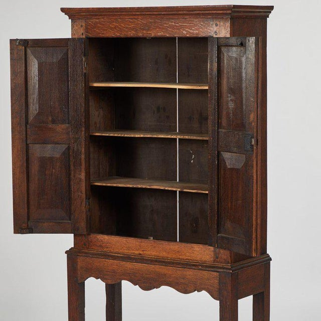 Originating in England, circa 1900. A hall cupboard in oak on stand.