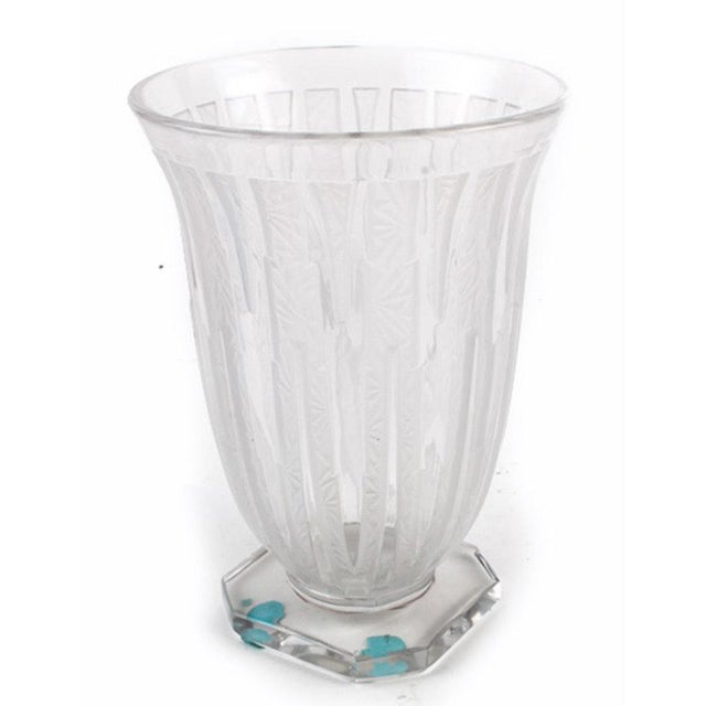 A Verlys art glass vase. This glass vase features a slightly flared rim, tapered body with lined accents, and a cut corner...