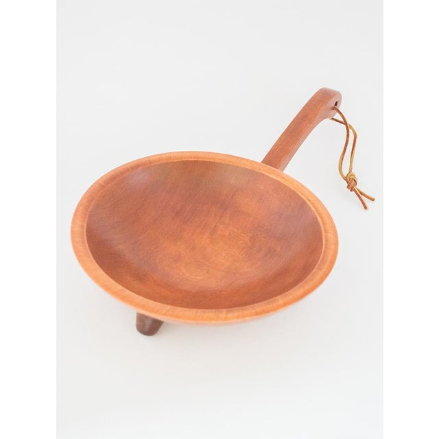 This 9-inch, oval footed Munising wooden bowl with handle and hanging cord hails from its namesake town, nestled on the...