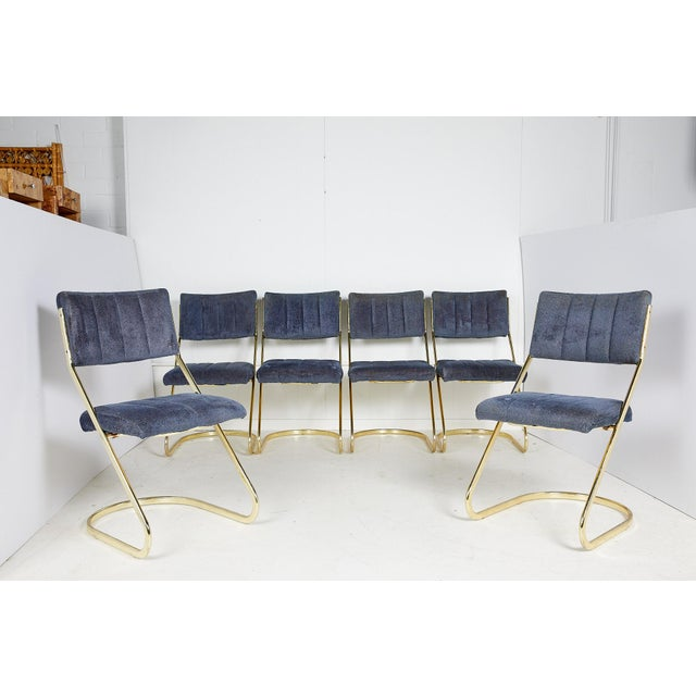 American midcentury set of six brass cantilever dining chairs by Douglas Furniture Corporation. The tubular brass frame is...