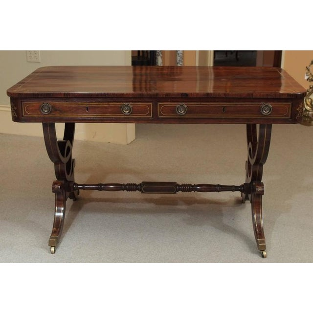 Antique English Regency rosewood writing table. Saber legs. Brass inlay.