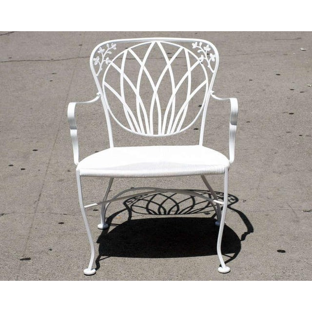 Woodard outdoor white painted iron armchairs with decorative Art Nouveau inspired scrolling floral motif along the back...