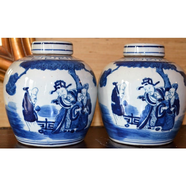 These are a set of beautiful indigo blue and bone white Chinoiserie Ginger Jars with a landscape and a Chinese Deities...