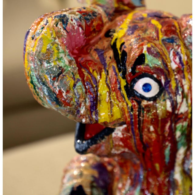 A whimsical and wonderful sculpture of a baby elephant playing. It is by the noted Brazilian American artist Mauro...