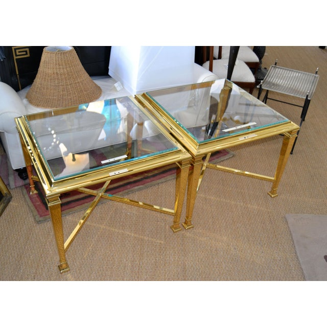 A pair of Hollywood Regency French Maison Jansen brass tables with glass tops. The set is ready for a new home.