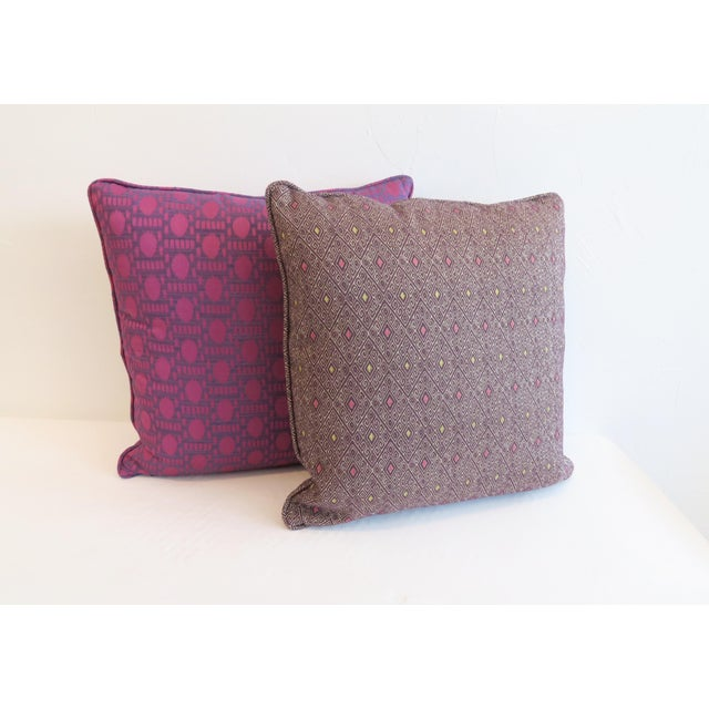 Pair of custom pillows in bright purple/magenta and deep plum patterns. Welt trim, zipper closure and synthetic down fill.