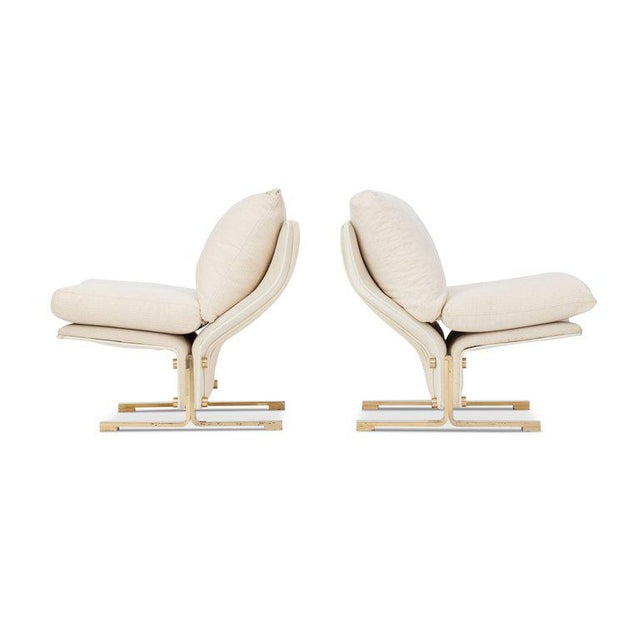 Two lounge chairs in white leather and brass. The chairs consist out of two pieces which are cleverly joined together. The...