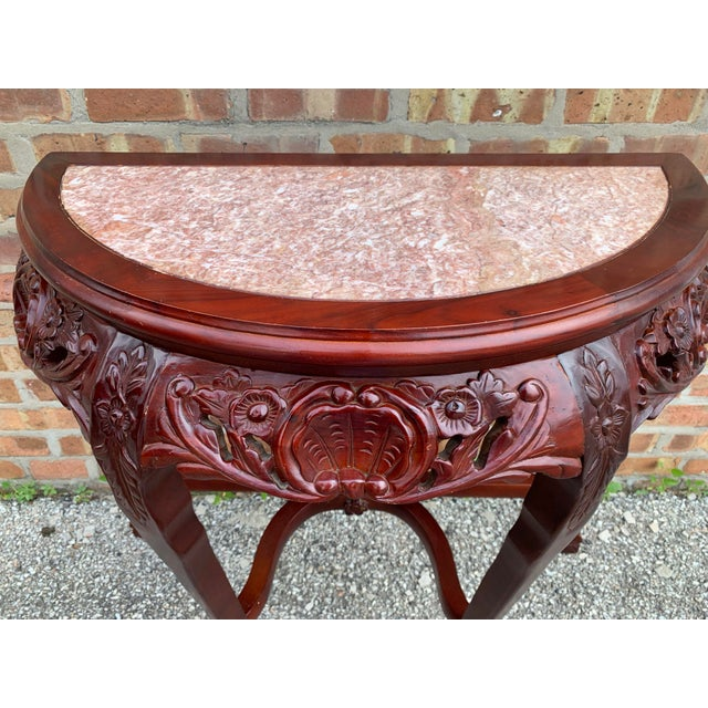 This is a gorgeous solid mahogany wood surmounted by a rose marble top demilune table with carved floral motifs across the...