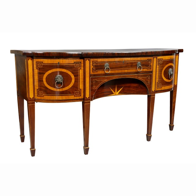 Bowed top with squared corners and central oval inlay and banded edge over a pair of cabinet doors and a central drawer...