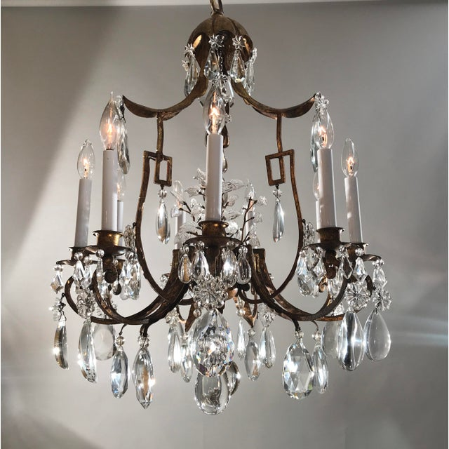 Circa 1930, French, Gilt Tole, Nine light Crystal Chandelier cast in an Asian motif. Shown with white candle sleeves...
