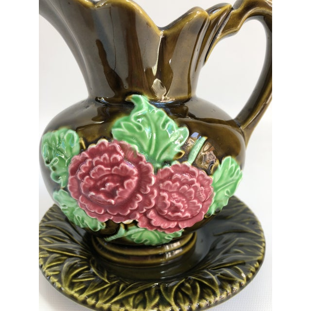 "1950s Majolica gravy boat with floral decoration and matching under-plate. Maker's mark on underside. Gravy boat, 5.25"" L..."