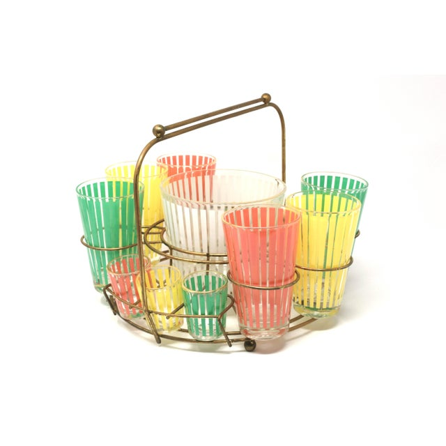 A set of six cocktail glasses and six shot glasses, each with pastel pink, yellow or green stripes and gold trim on the...