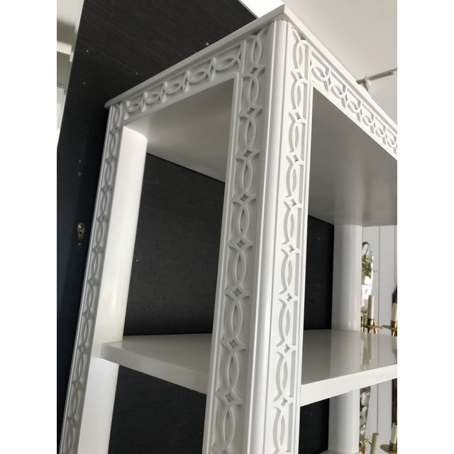 Elegant tall painted creamy white wood multi shelf étagère having lattice inspired carved decoration and four adjustable...