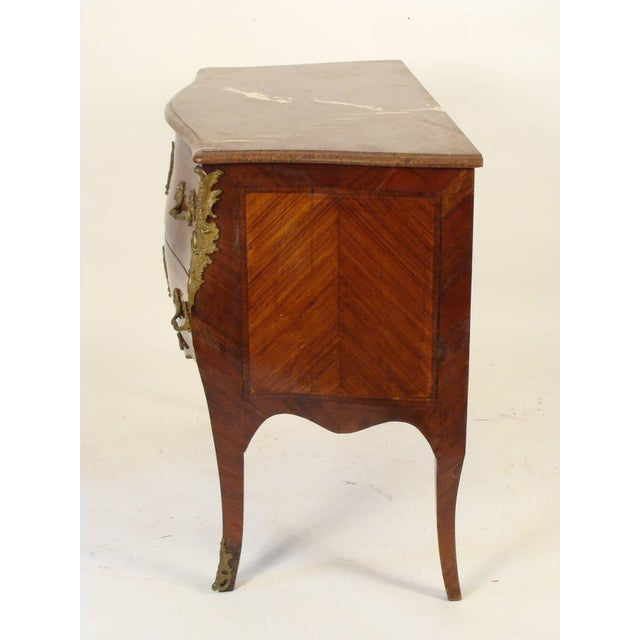 Louis XV style tulipwood, kingwood and mahogany, ormolu-mounted bombe commode with a marble top, circa 1880.