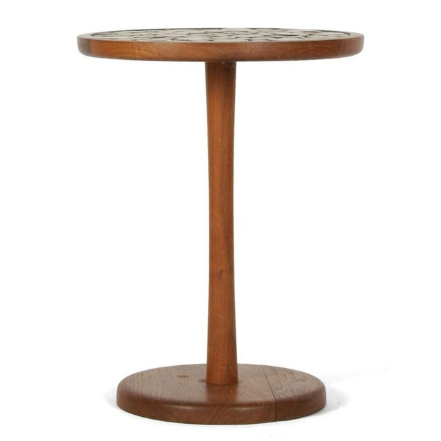 A pedestal side table with a round top inlayed with ochre colored circular ceramic tiles in various diameters, the top...