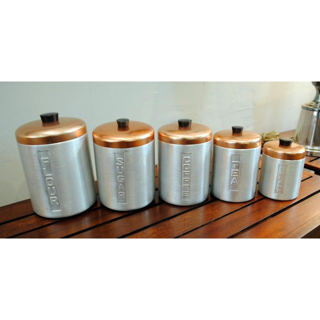 Very cool and clean set of Nesting Aluminum Kitchen Canisters from the 1950's. Copper plated tops with hard plastic black...