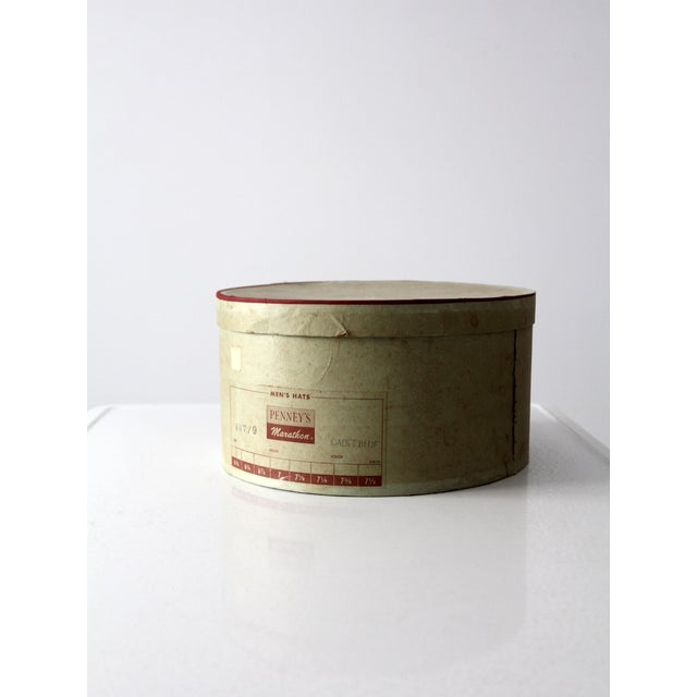 A 1950s vintage hat box for a Penney's Marathon men's hat. The olive green paper board storage box features maroon trim...