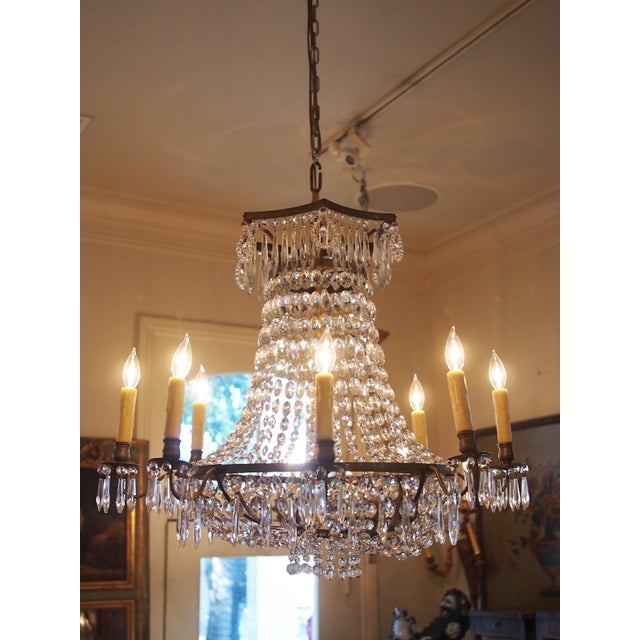 An Italian, Empire style chandelier with a wide crown transitioning to eight arms and finished with a shallow basket...