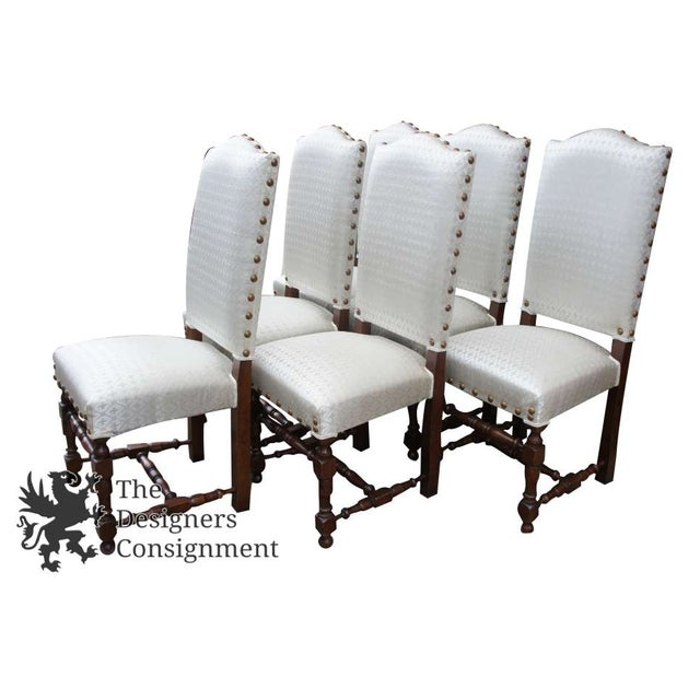 A beautiful set of old world Spanish/ Jacobean style dining chairs. Made from oak and finished with a Fleur-de-lis...