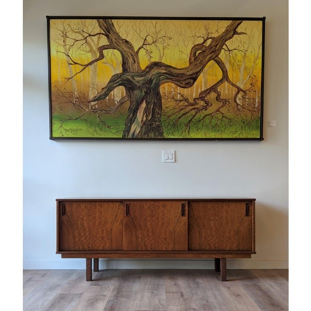 This Dyrlund teak credenza has three sliding doors with two compartments having adjustable shelves and the last...