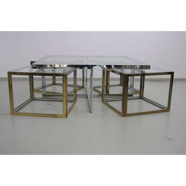 Rare Maison Charles brass coffee table with 4 nesting tables in brass and chrome. The glass plates are loosely inserted to...