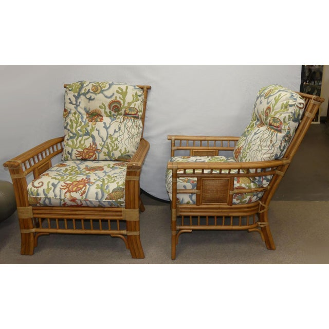 A gorgeous pair of rattan armchairs by Coastal Creations. Rattan frames with leather wrapped accents and woven wicker...