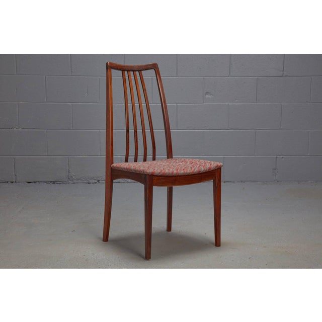 These dining chairs feature an sculptural rosewood frame, an elegant high back with four thin spindles, and patterned...