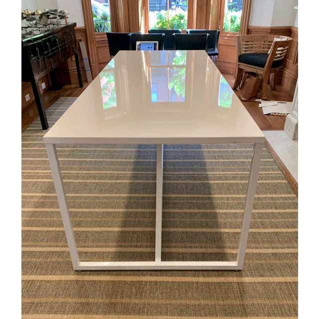 Sleek and sophisticated, the Stut table from comfortable sits 8. The top is white lacquered wood and it features powder-...