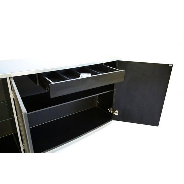 Painted metal buffet with black glass as a surface. The front of the buffet is curved, and has rounded soft edges on the...
