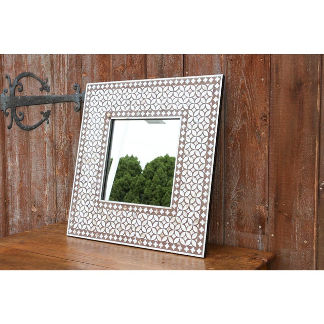 An exquisite wall art piece, this wood mirror features a beautiful geometric mother of pearl inlaid pattern in lustrous hues.