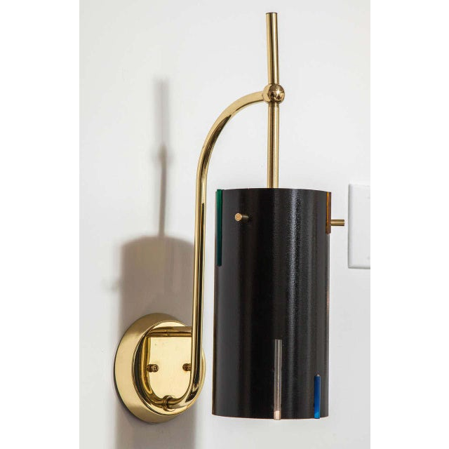 Pair of Mid-Century Italian sconces with polished brass arm and backplate, and black lacquer. This pair has been restored...
