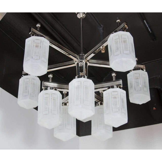 This beautiful Art Deco style chandelier in polished nickel features ten arms and nine relief etched frosted glass globes...