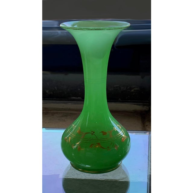 A beautiful green opaline vase with gilt scrolls from France.