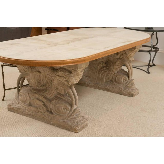 An exceptional table with carved-stone, dolphin-motif base. Wood and vellum parchment oval top. Maison Jansen France,...