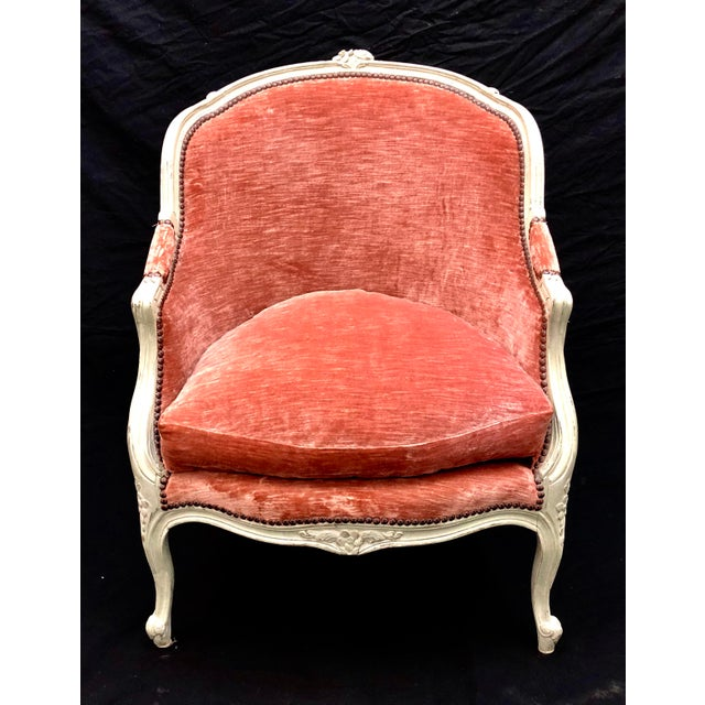 Excellent restored bergere chair with dusty rose/coral velour upholstery. Nailhead trim and shabby chic off white paint...
