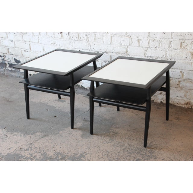 An outstanding pair of two-tiered side tables or nightstands designed by Bertha Schaefer for Singer & Sons. The tables...