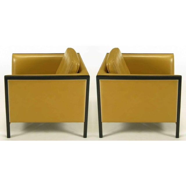 Pair of Stow Davis of Grand Rapids Michigan, even arm club chairs in camel leather with ebonized ashwood framing and...
