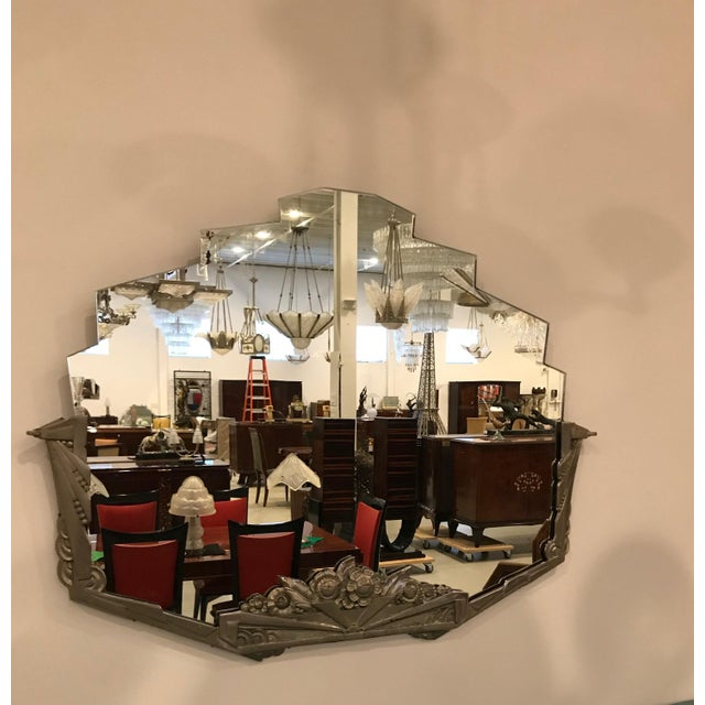 French Art Deco wall mirror with geometric and floral motif details. The frame has modest wear with signs of some patina....