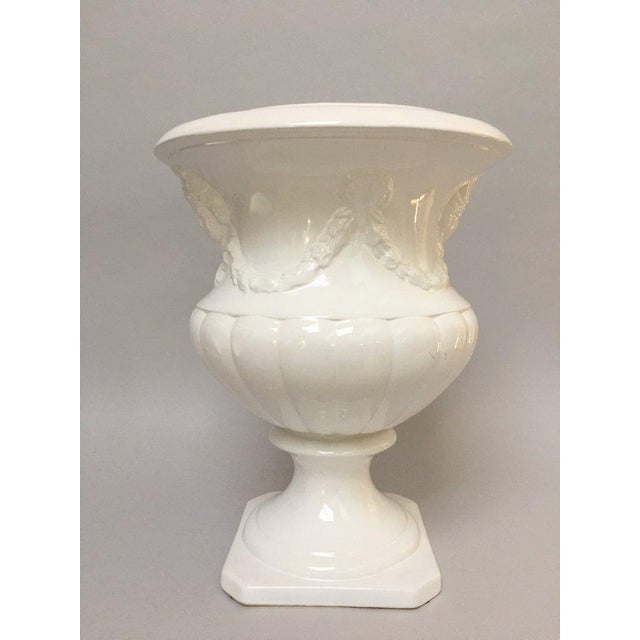 Very large white porcelain Neo-classical urn form planter with raised relief female face and garland. The urn measures...