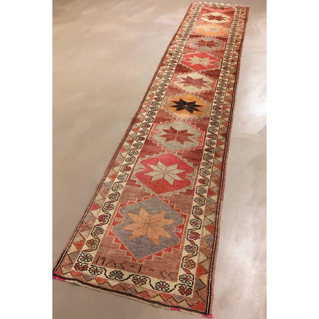 An old hand-knotted Anatolian wool rug. Repeating eight-pointed stars. The rug overall has the faded look that comes with...