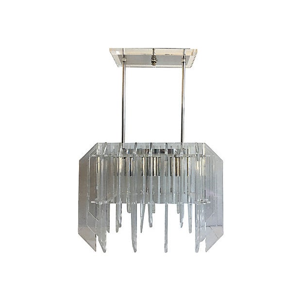 Spectacular 1970s modern Lucite skyscraper chandelier featuring staggered and beveled Lucite fins in a rectangular shape...
