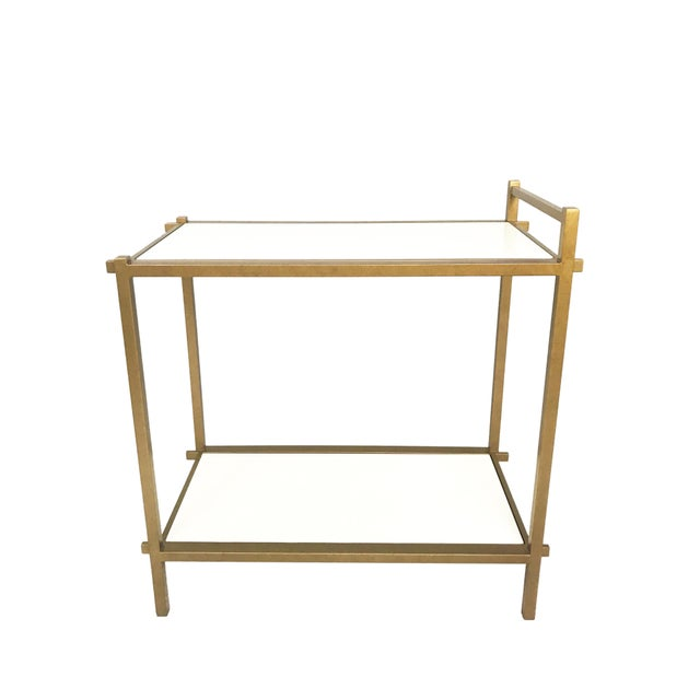 Beautiful double decker bar cart featuring thick white colored top and antique Gold Finish on the iron frame. Floor sample...