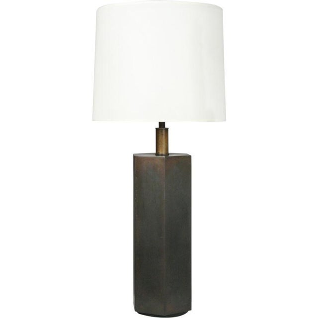 A geometric table lamp in a hexagon column form in antique bronze patina finish raised on a circular base. By Chapman,...
