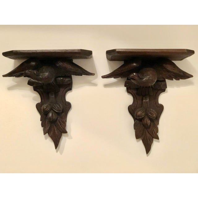 """Pair of decorative wood wall brackets. An eagle on a branch with spread wings """"holds"""" the shelf; carved fruit and leaf..."""